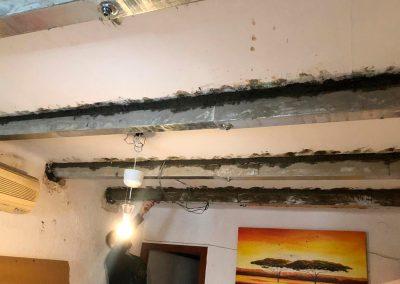 Operario instalando chapa metálica en viga con aluminosis